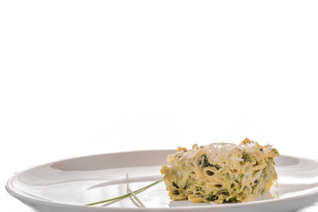 Detail of delicious food vegetarian food baked pasta with parmesan, close up, creative food with basil  White background