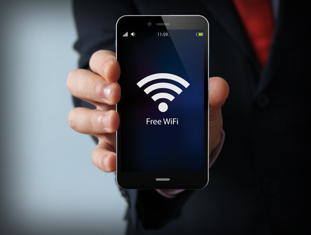 business and mobility communications concept: businessman holding a modern smartphone with free wifi zone icon Stok Fotoğraf