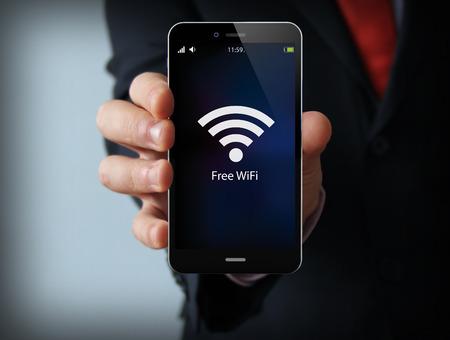 negócios e comunicações conceito de mobilidade: empresário segurando um smartphone moderno com o ícone de zona livre wi-fi