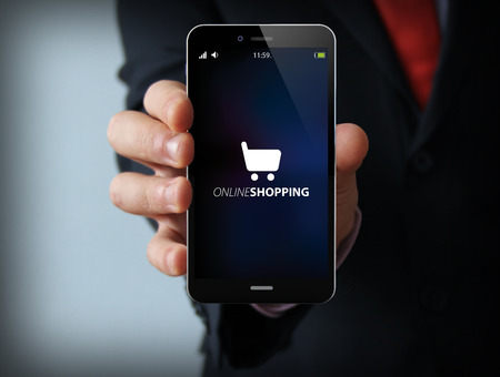 telecom: business and mobility communications concept: businessman holding a modern smartphone with online shopping icon