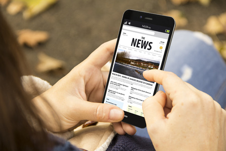 メディア技術と現代的なライフ スタイル コンセプト: 公園でニュースを読むスマート フォンを持つ若い女性