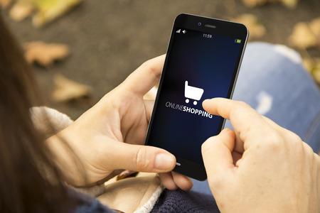 comprando: concepto de negocio m�vil: Manos femeninas usando el tel�fono inteligente para ir de compras en l�nea