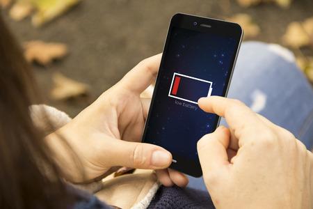 pila: concepto de energía: La hembra que usa el teléfono inteligente con batería baja Foto de archivo