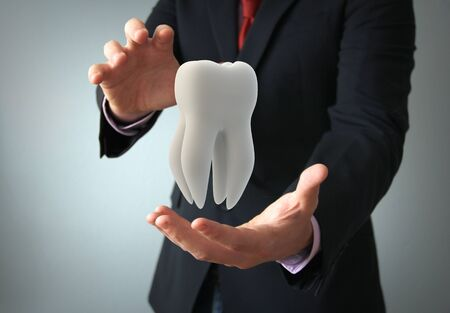dental insurance: dental insurance concept: businessman protecting a tooth with his hands