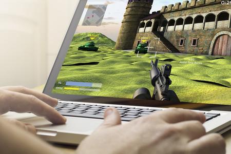 jugar: concepto de juego: el hombre con un ordenador portátil para jugar juego de guerra Foto de archivo