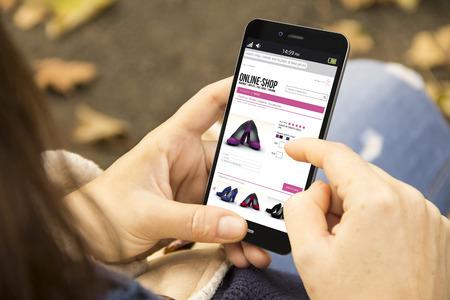 lifestyle: entreprise et le concept de style de vie moderne: jeune femme achats en ligne dans le parc Banque d'images