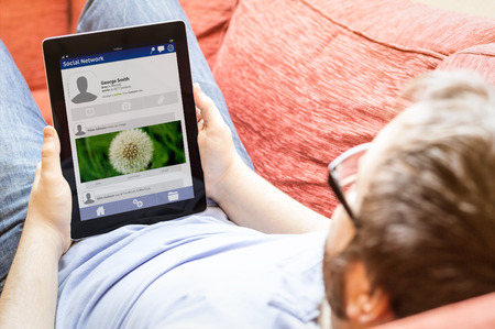 web pages: social network concept: man holding a tablet on the sofa with a social network page in the screen Stock Photo