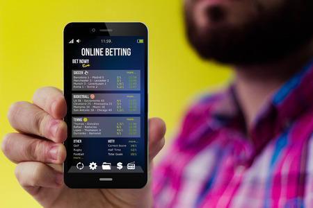 checked shirt: lifestyle and technology: Hipster with beard and checked shirt holding a smartphone with betting online app