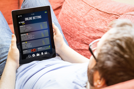 bet online concept: hipster man betting online on a tablet at the sofa Foto de archivo