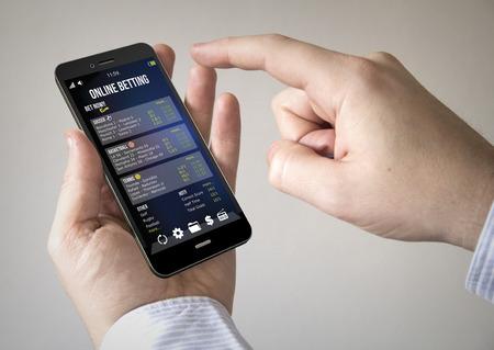 賭けオンライン アプリケーションとモバイルのスマート フォンを使用している人のクローズ アップ