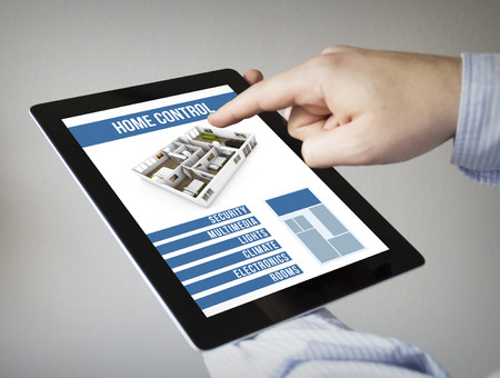 smart home: new technologies concept: hands with touchscreen tablet with smart home control app