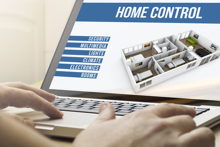 telecommuting: smart home concept: man using a laptop with house automation software on the screen Stock Photo