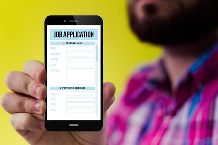 checked shirt: job search concept: Hipster with beard and checked shirt holding a smartphone with online job application form on the screen Stock Photo
