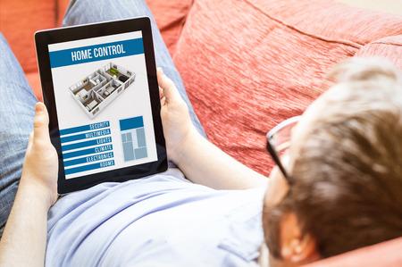 domotique: la technologie vie notion: hippie sur le canap� avec l'application de contr�le domotique