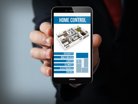 automation: house automation concept: businessman hand holding a touch phone with smart home control application on the screen