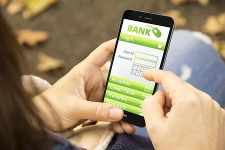 銀行のセキュリティ概念: 公園で携帯電話のオンライン銀行業務アプリケーションを持つ若い女性 写真素材