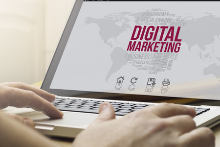 marketing digital concept: man using a laptop with computer generated digital marketing interface on the screen Stock Photo