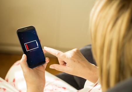 bateria: energía y moderno concepto de estilo de vida: mujer joven con una interfaz de baja batería en un 3d generaron smartphone. Todos los gráficos de pantalla componen.
