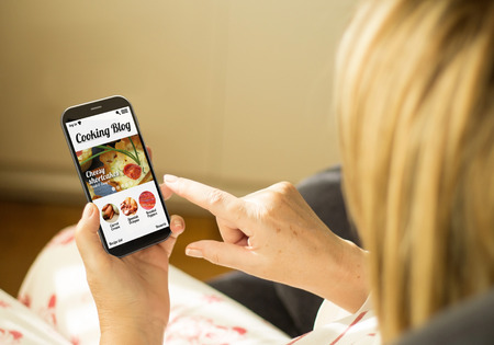 modern lifestyle concept: mature woman with 3d generated touchscreen smartphone with a cooking blog on the screen