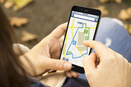 navegacion: gps y el turismo concepto: mujer que sostiene un 3d generado smartphone con aplicación de navegación en la pantalla. Gráficos en pantalla se componen. Foto de archivo