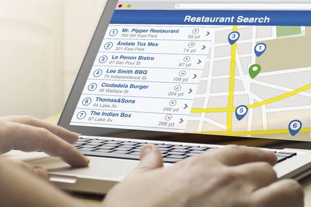 search result: restaurant search concept: man using a laptop with restaurant search software on the screen. All screen graphics are made up. Stock Photo