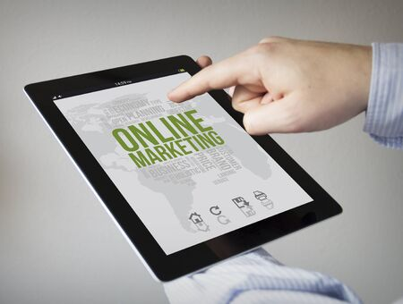 new technologies: new technologies concept: hands with touchscreen tablet with online markting on the screen. Screen graphics are made up.