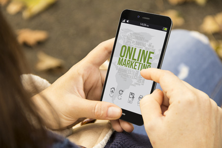 digital business concept: woman holding a 3d generated smartphone with online marketingon the screen. Graphics on screen are made up. Stockfoto