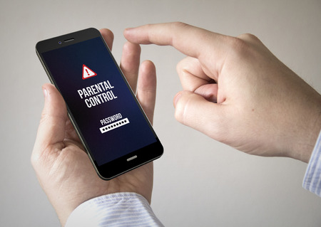 parental control: Close up of man using 3d generated mobile smart phone with parental control on the screen. Screen graphics are made up. Stock Photo
