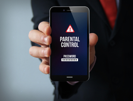 parental control: new technologies protection concept: businessman hand holding a 3d generated touch phone with parental control on the screen. Screen graphics are made up.
