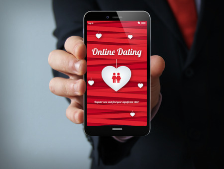 dating couples: new technologies relationship concept: businessman hand holding a 3d generated touch phone with online dating on the screen. Screen graphics are made up.