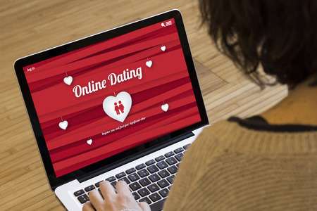 dating couples: dating online concept: online dating website on a laptop screen. Screen graphics are made up. Stock Photo