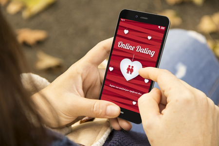 couple dating: find love and technology concept: woman holding a 3d generated smartphone with online dating website on the screen. Graphics on screen are made up. Stock Photo
