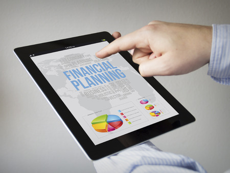 new technologies: new technologies and plan concept: hands with touchscreen tablet with financial planning on the screen. Screen graphics are made up.