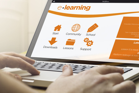 platforms: online training concept: man using a laptop with e-learning platform on the screen. Screen graphics are made up. Stock Photo