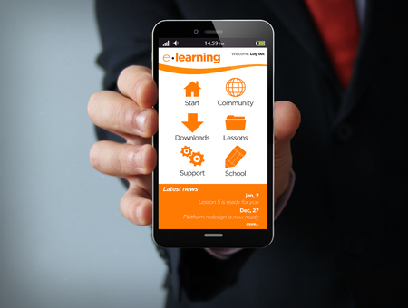 learning: new technologies education concept: businessman hand holding a 3d generated touch phone with e-learning platform on the screen. Screen graphics are made up.