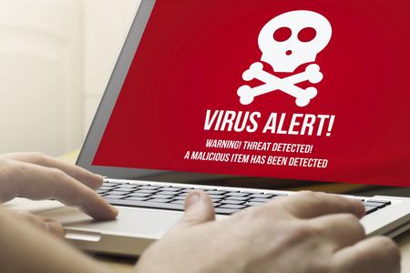beveiliging concept: man met behulp van een laptop met een virus alert op het scherm. Screen graphics zijn opgebouwd.