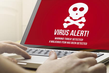 technology security: security concept: man using a laptop with virus alert on the screen. Screen graphics are made up.