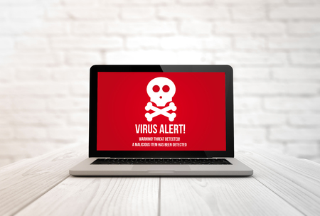 security concept: digitally generated laptop on a wooden table with virus alert. Screen graphics are made up.