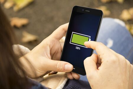 bateria: concepto de energía: Mujer que sostiene un teléfono inteligente 3D generados con el icono de batería llena en la pantalla. Los gráficos en la pantalla se componen.