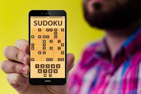 checked shirt: digital gaming concept: Hipster with beard and checked shirt holding a smartphone with sudoku application form on the screen Stock Photo