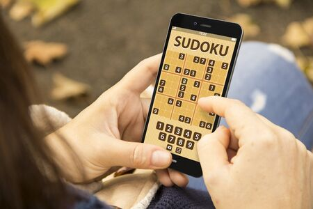 sudoku: young woman with sudoku game application phone at the park