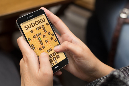 sudoku: woman playing sudoku game at smartphone Stock Photo
