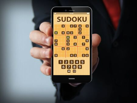 sudoku: Businessman with game on the screen