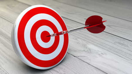 intentions: strategic business solutions, marketing or corporate strategy concept: digital generated dart in the center of a red target, modern wooden background. Stock Photo