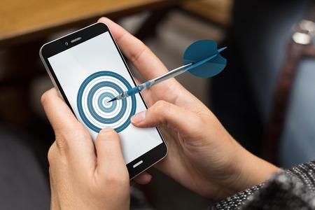 mobile Werbung, Marketing oder Ziele Konzept: Mädchen, das einen digital generierte Telefon mit Ziel auf dem Bildschirm. Alle Bildschirmgrafik zusammensetzen.