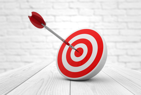 target shooting: strategic business solutions or corporate strategy concept: digital generated dart in the center of a red target, modern wooden and bricks background. Stock Photo