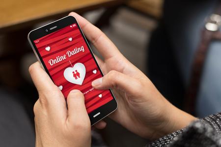 Online-Liebe-Konzept: Mädchen, das auf dem Bildschirm ein digitales generiert Telefon mit Dating-Website. Alle Bildschirmgrafiken bestehen. Standard-Bild