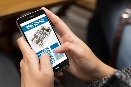 smart home-Konzept: Mädchen, das einen digitalen erzeugt Telefon mit Home-Automation-App auf dem Bildschirm. Alle Bildschirmgrafik zusammensetzen.