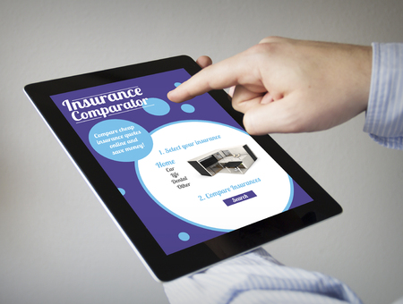 new technologies concept: hands with touchscreen tablet with insurance comparator on the screen. Screen graphics are made up.