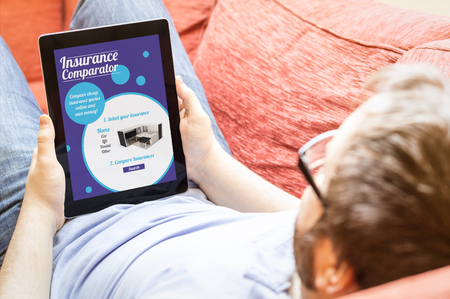 technology lifestyle concept: hipster on the sofa with  insurance comparator tablet. Screen graphics are made up.